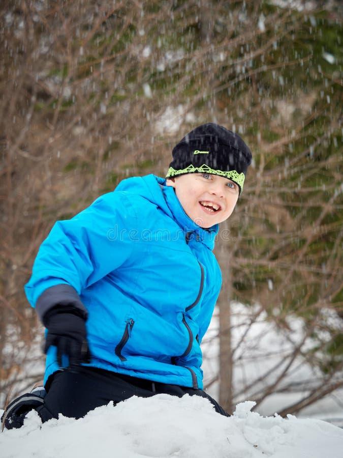 El muchacho lanza una bola de nieve imágenes de archivo libres de regalías