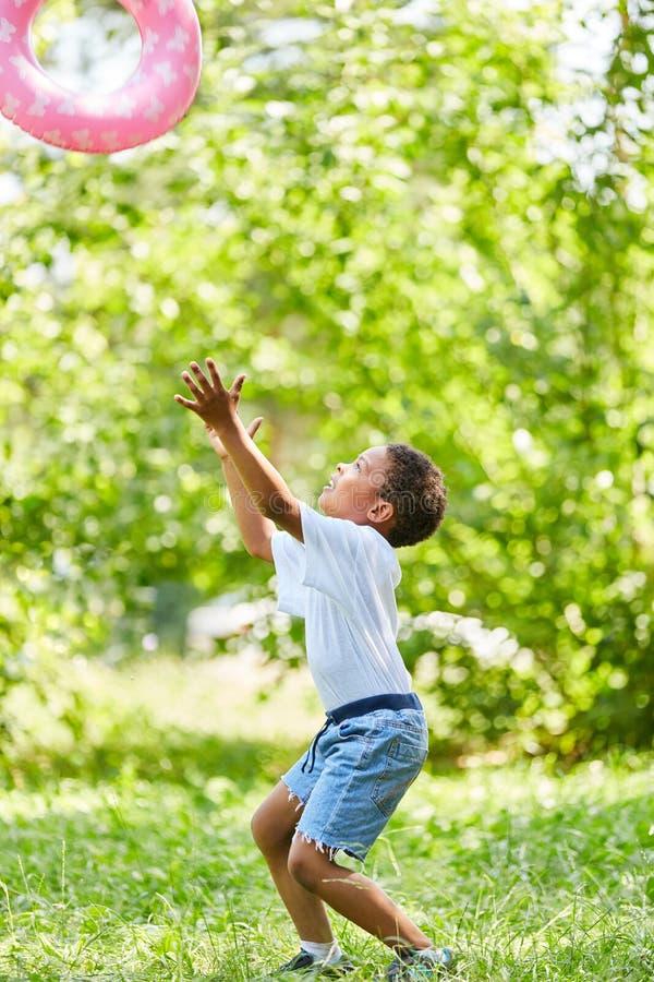 El muchacho lanza y coge un anillo que nada fotos de archivo