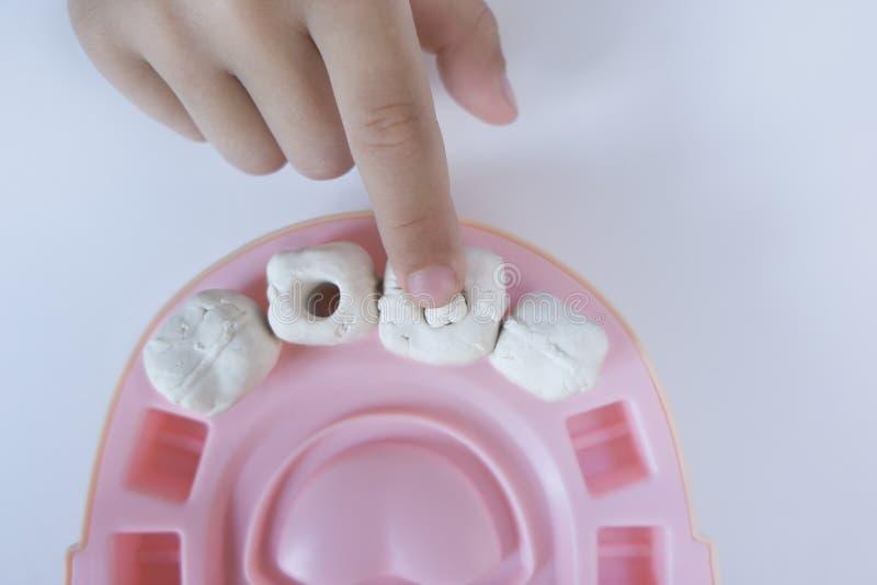 El muchacho 5let pasa la diversión del tiempo en casa y útil, él juega al dentista y pone rellenos en los dientes, se esculpen qu imagen de archivo libre de regalías