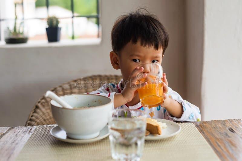 El muchacho lindo asiático tiene el desayuno y zumo de naranja imagen de archivo