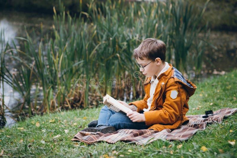 El muchacho lindo camina y presenta en un parque colorido del otoño imagen de archivo