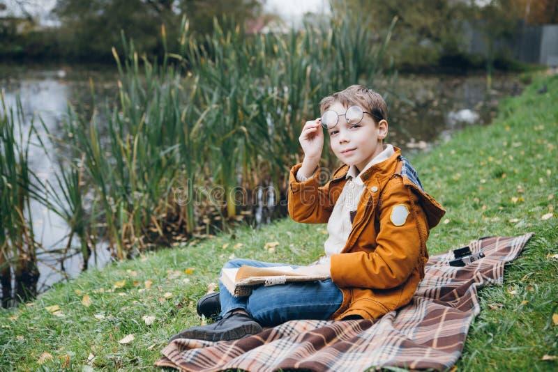 El muchacho lindo camina y presenta en un parque colorido del otoño fotos de archivo