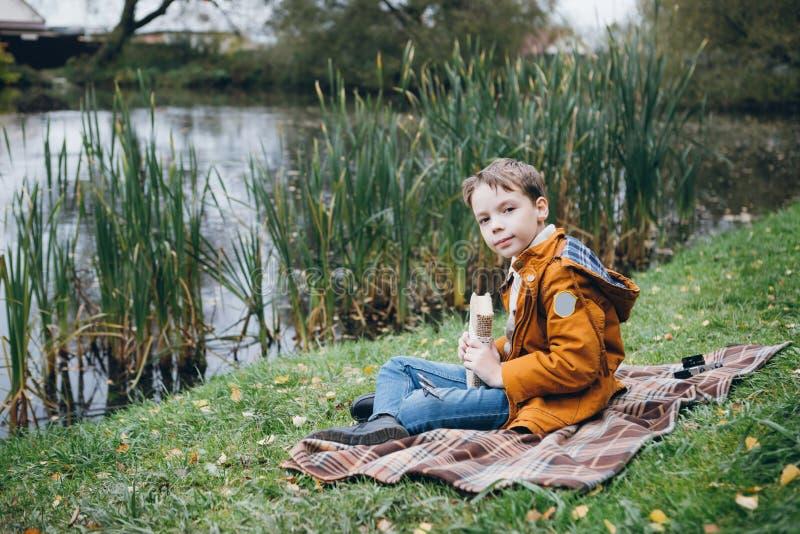 El muchacho lindo camina y presenta en un parque colorido del otoño imagenes de archivo