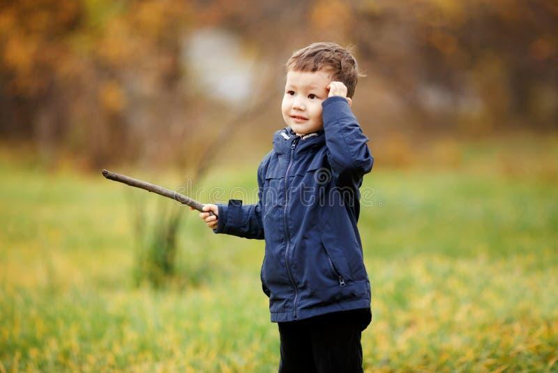El muchacho lindo con el palillo de madera en su mano que juega en el otoño parquea al aire libre Confuso, pensando qué hacer, mi foto de archivo libre de regalías