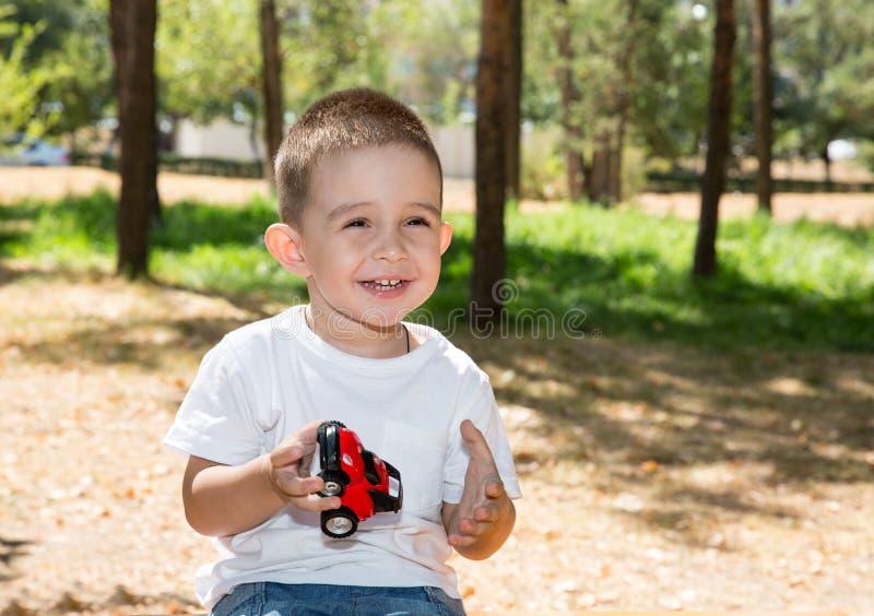 El muchacho lindo del pequeño niño juega con el coche del juguete en parque en la naturaleza en el verano imagen de archivo libre de regalías