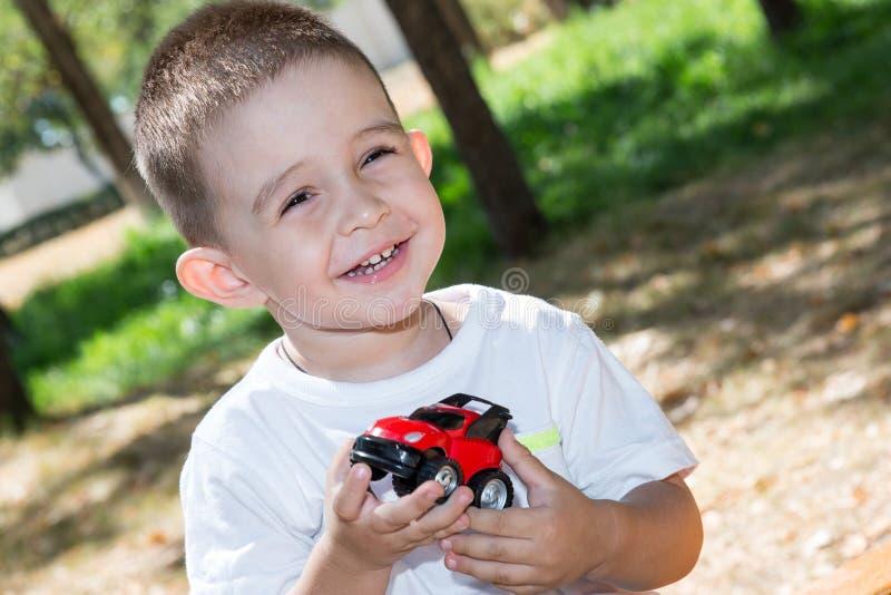 El muchacho lindo del pequeño niño juega con el coche del juguete en parque en la naturaleza en el verano fotos de archivo