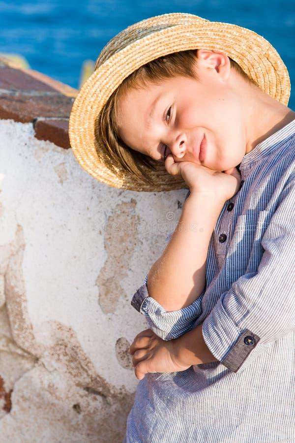 El muchacho lindo en sombrero de paja sonríe contra el mar imagen de archivo libre de regalías
