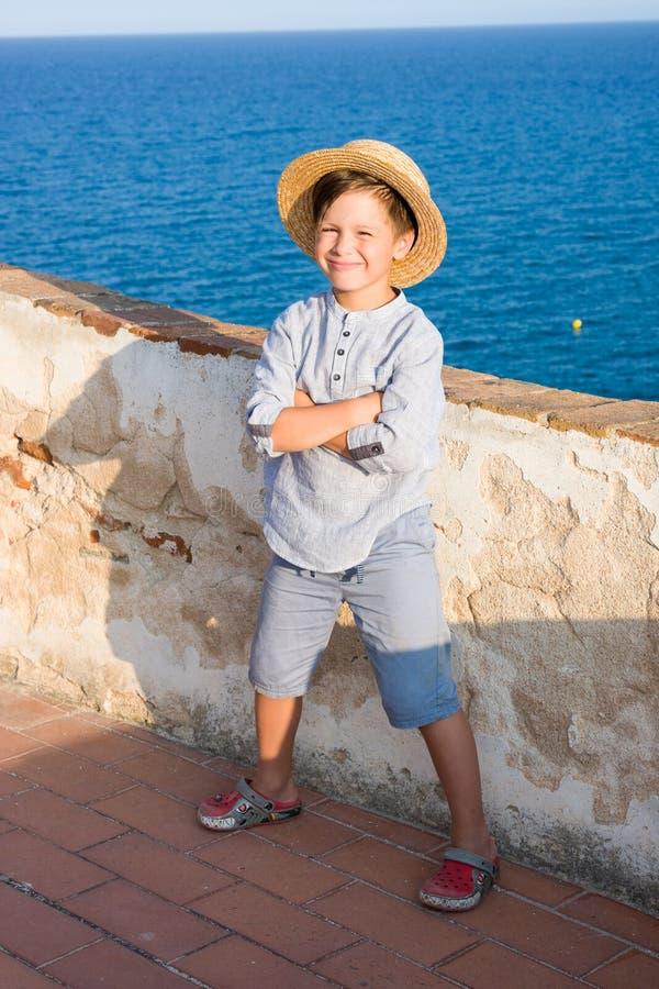 El muchacho lindo en sombrero de paja sonríe contra el mar foto de archivo