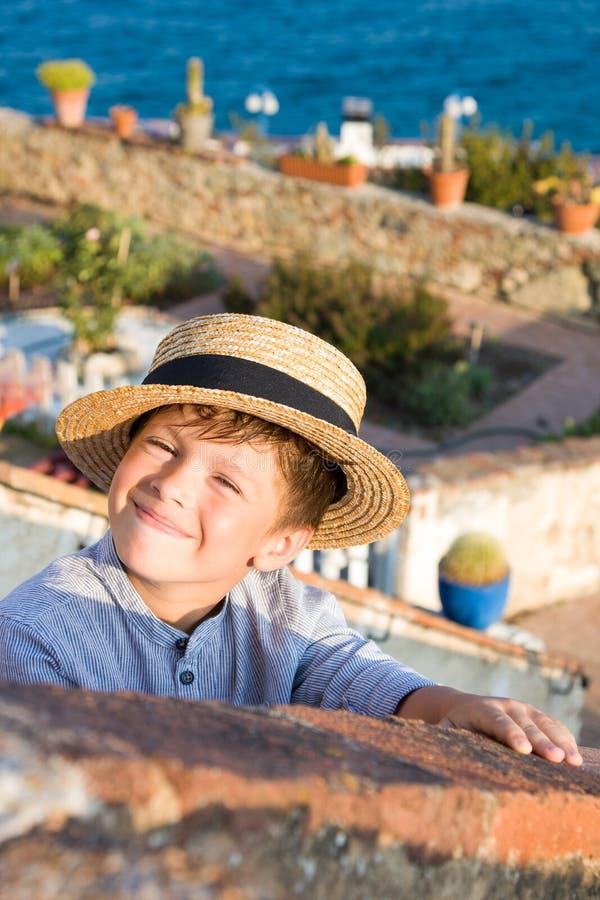 El muchacho lindo en sombrero de paja sonríe contra el mar fotos de archivo