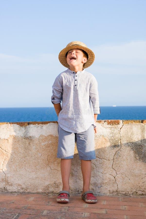 El muchacho lindo en sombrero de paja sonríe contra el mar imágenes de archivo libres de regalías
