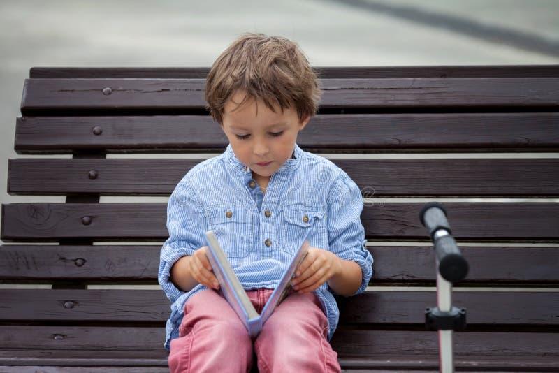 El muchacho lindo, leyó un libro en el parque, sentándose en banco, verano imagenes de archivo