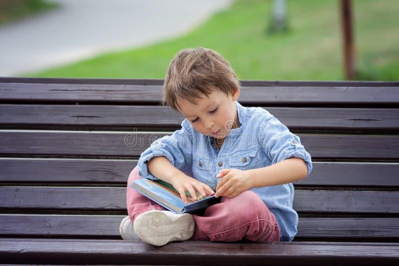 El muchacho lindo, leyó un libro en el parque, sentándose en banco, verano fotografía de archivo libre de regalías