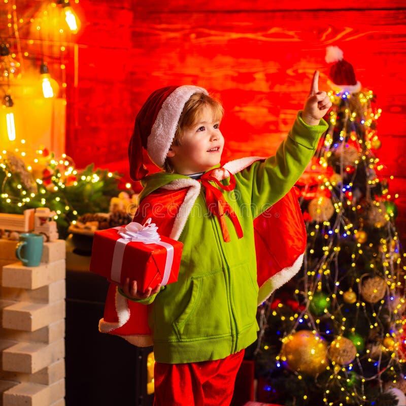 El muchacho lindo muestra un finger en la luz de la Navidad Santa Claus Workshop foto de archivo libre de regalías