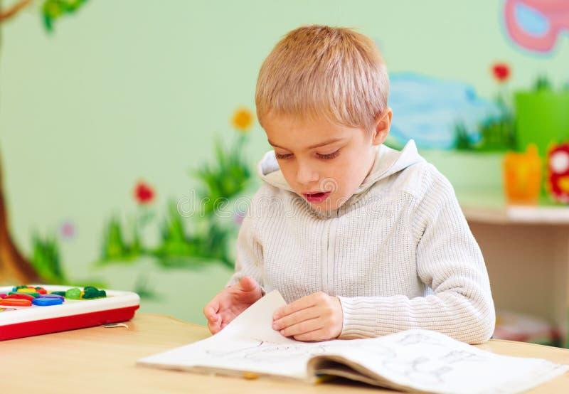 El muchacho lindo, niño con el special necesita mirar un libro, en centro de rehabilitación foto de archivo