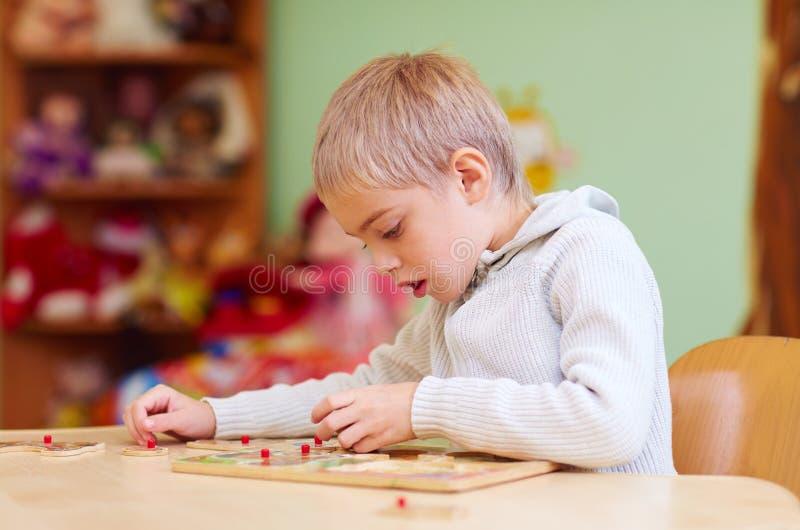 El muchacho lindo, niño con el special necesita solucionar un rompecabezas en centro de rehabilitación fotografía de archivo