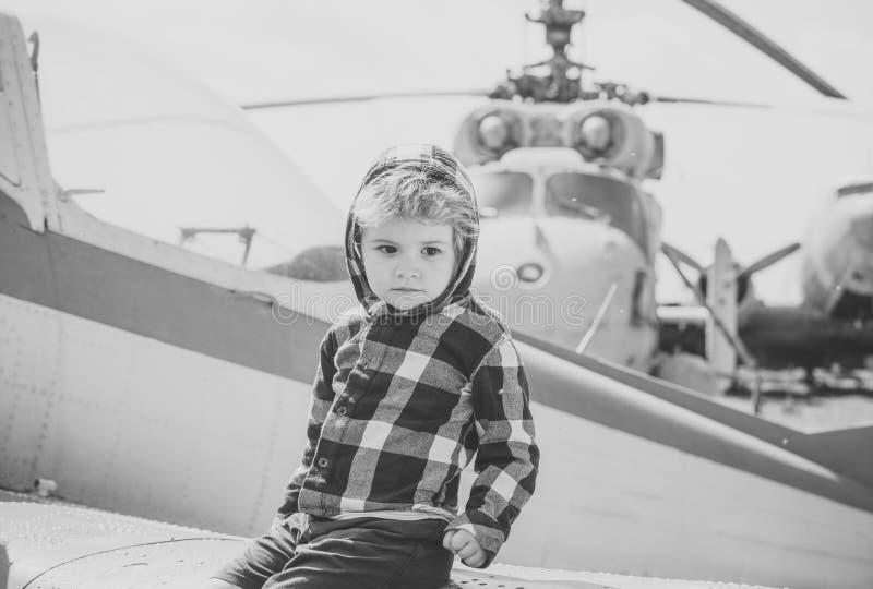 El muchacho lindo se sienta en el ala del viejo avión en museo de la aviación Helicóptero y cielo viejos texturizados del grunge  fotos de archivo libres de regalías