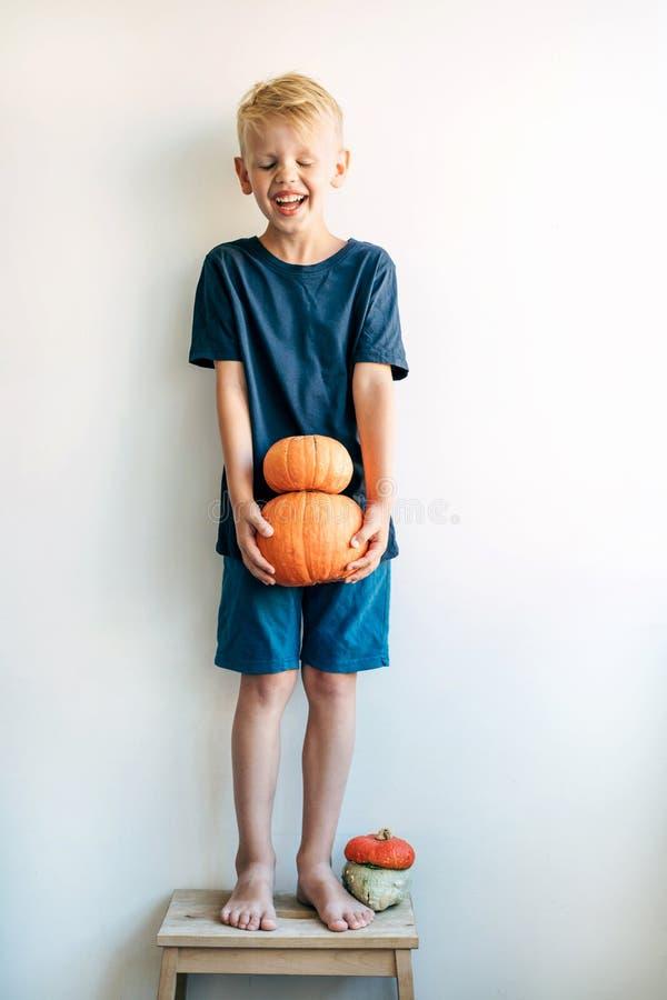 El muchacho lleva a cabo dos calabazas y risas maduras por completo imagen de archivo libre de regalías