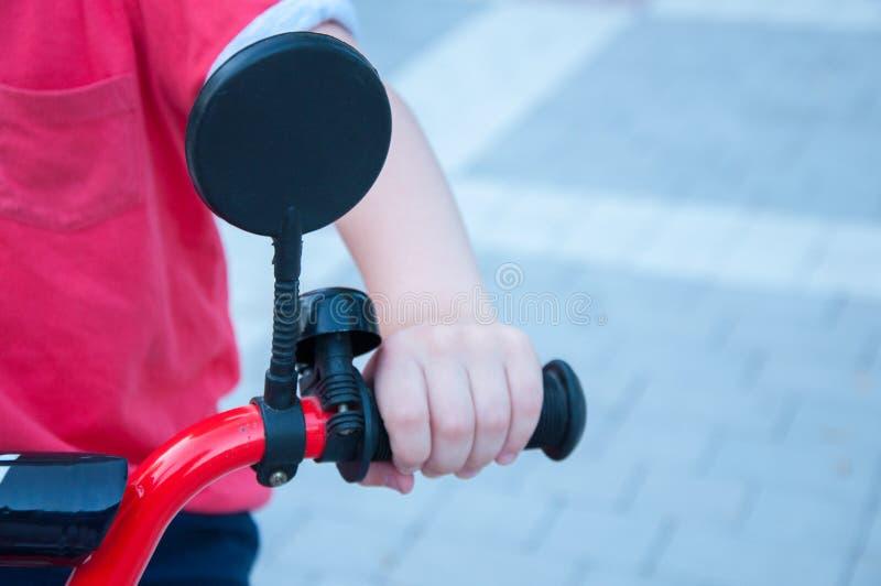 El muchacho lleva a cabo la mano en la bicicleta Espejo en el volante En el parque imagen de archivo libre de regalías