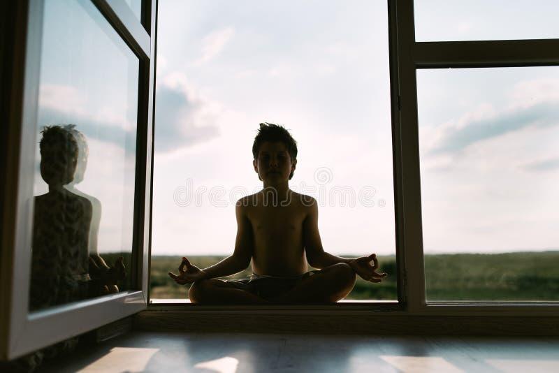 El muchacho medita en la posición de loto fotos de archivo libres de regalías