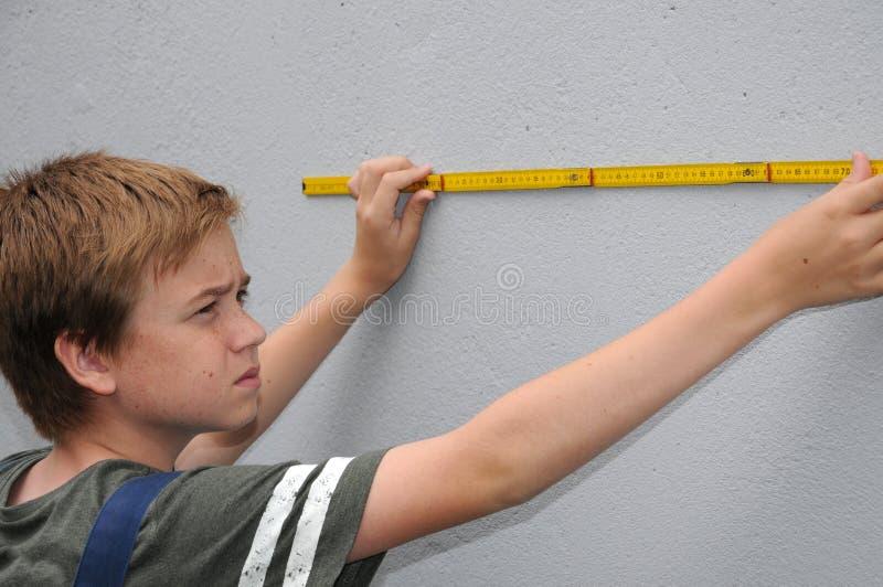 El muchacho mide la pared con la ayuda de un metro plegable imagen de archivo