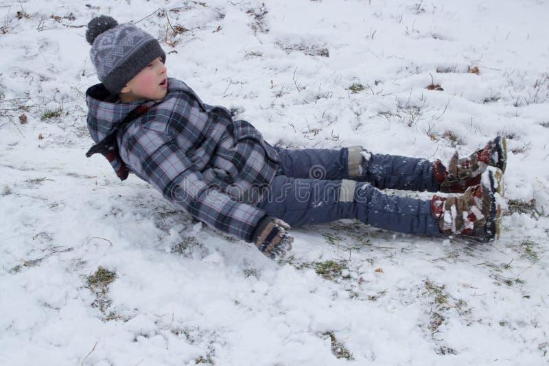 El muchacho miente en la nieve imagen de archivo