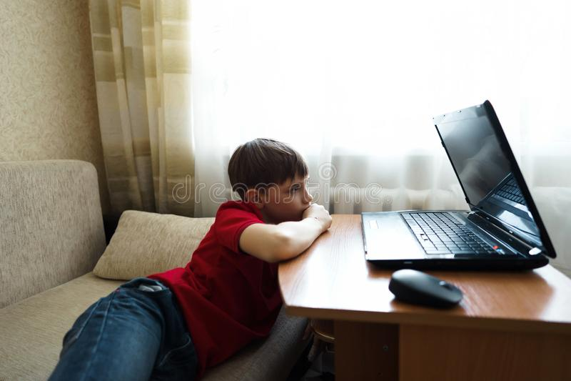 El muchacho miente en la sala de estar en el sofá y mira una película en un ordenador portátil fotografía de archivo libre de regalías
