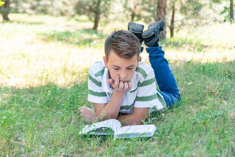 El muchacho miente en el parque en la hierba y está estudiando en la naturaleza, educación y la ciencia, el libro está mintiendo  fotografía de archivo libre de regalías