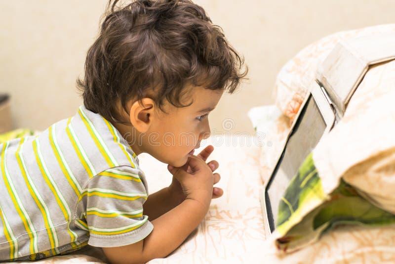 El muchacho mira el iPad imagen de archivo libre de regalías