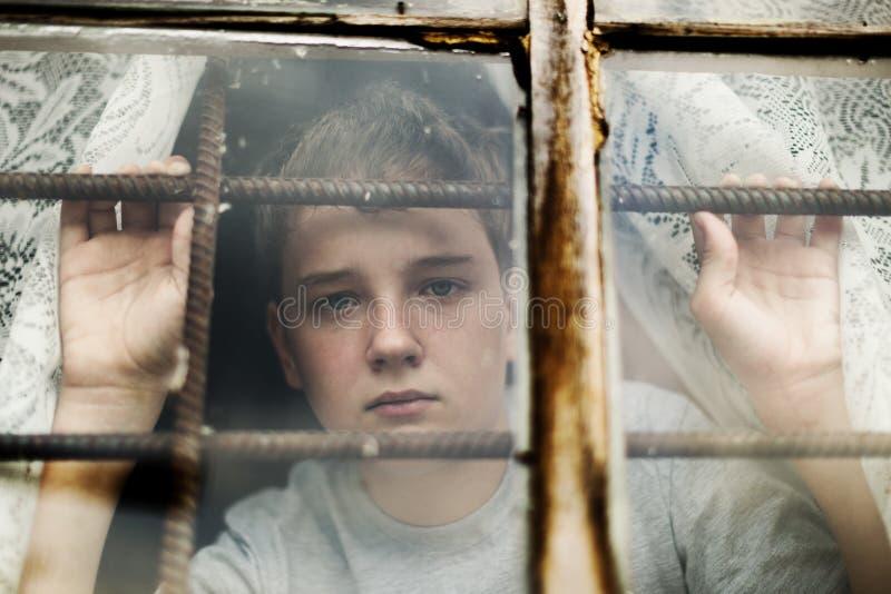 El muchacho mira fuera de la ventana a través de un enrejado imagen de archivo libre de regalías