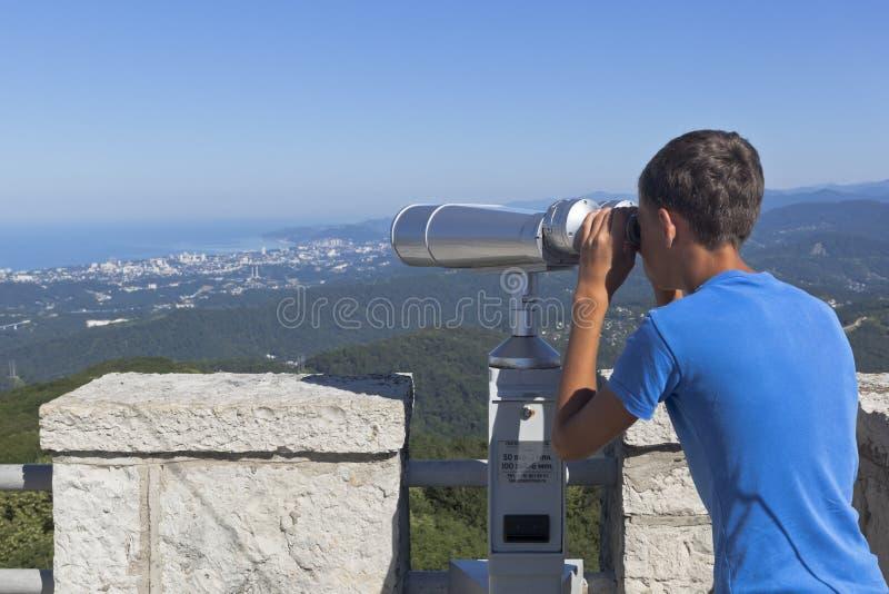 El muchacho mira a la ciudad de vacaciones de Sochi a través de los prismáticos de una torre en la montaña Ahun grande imagen de archivo libre de regalías