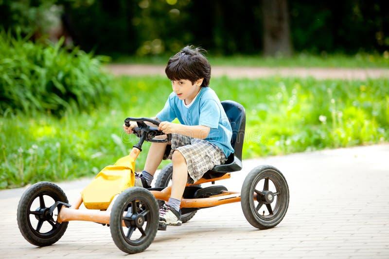 El muchacho monta un velomobile fotografía de archivo