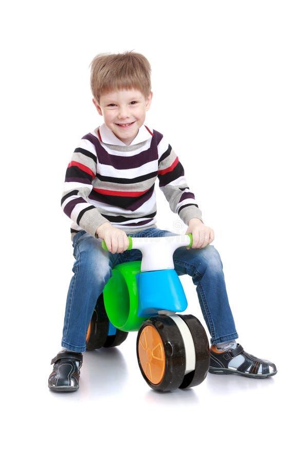 El muchacho monta una bicicleta fotografía de archivo libre de regalías