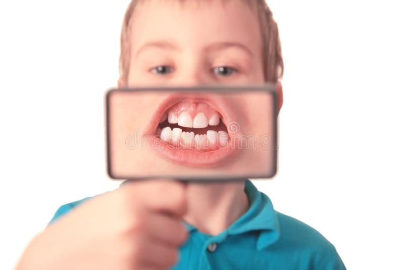 El muchacho muestra los dientes a través de la lupa imagen de archivo