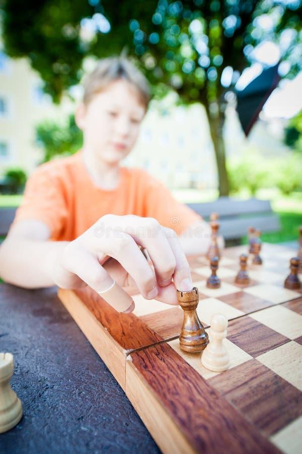 El muchacho mueve el pedazo en ajedrez fotos de archivo libres de regalías