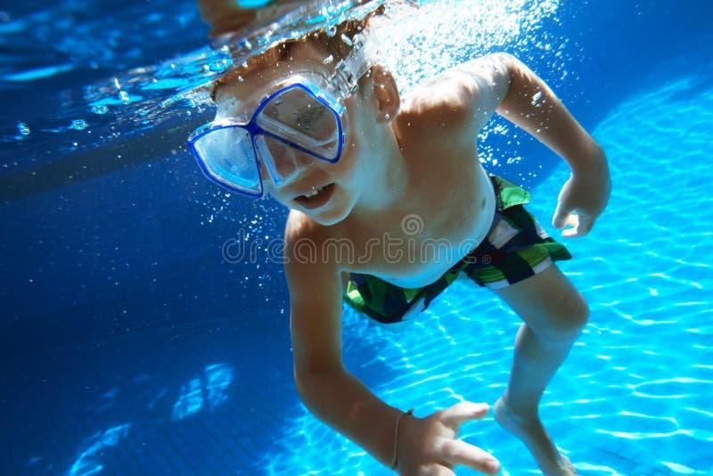 El muchacho nada bajo el agua con la máscara del tubo respirador imagen de archivo libre de regalías