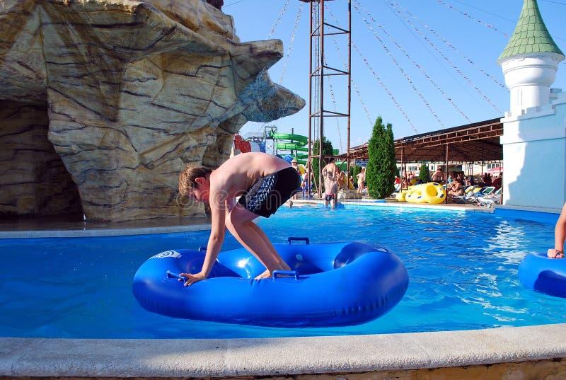 El muchacho nada en la piscina con un anillo de goma en aquapark debajo del cielo abierto fotografía de archivo libre de regalías