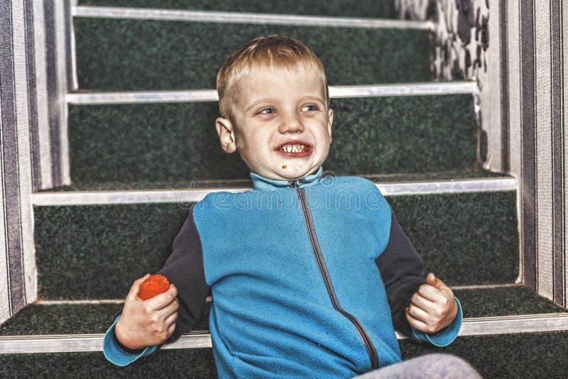 El muchacho, niño, feliz, sonrisa, risa, bebé, come, las zanahorias, en casa fotos de archivo