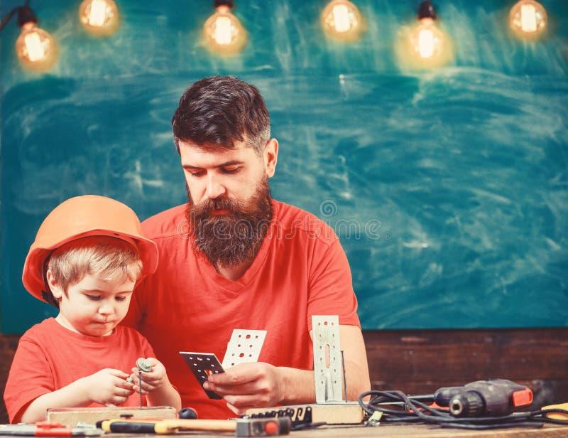 El muchacho, ni?o en casco protector hace a mano, reparando, hace artes con el pap? Padre como concepto de la manitas padre fotos de archivo libres de regalías