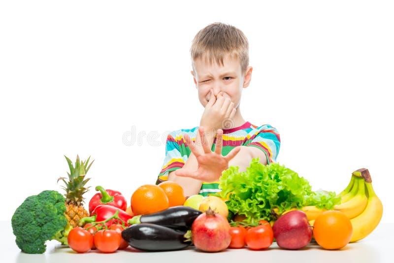 El muchacho no hace como las verduras y las frutas, repugnancia para la foto del concepto de la comida foto de archivo libre de regalías