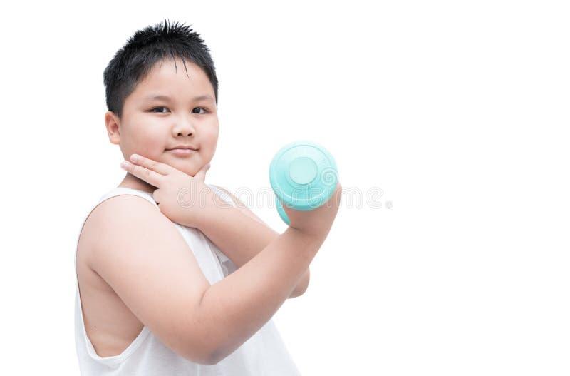 El muchacho obeso hermoso está haciendo ejercicios con pesas de gimnasia foto de archivo