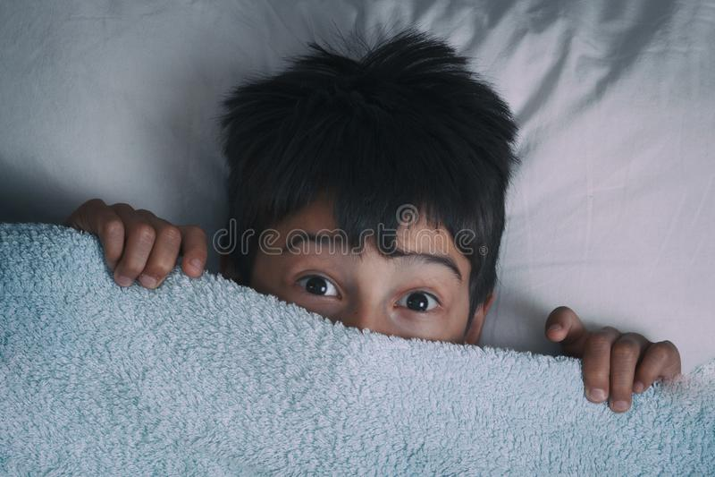 El muchacho para el miedo en una cama, el concepto de pesadillas fotografía de archivo
