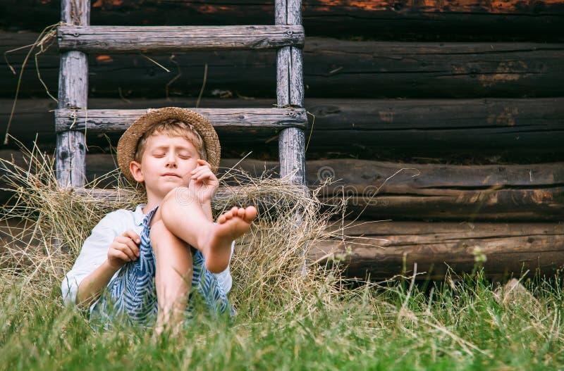 El muchacho perezoso miente en la hierba debajo del granero - verano descuidado en cuenta fotografía de archivo libre de regalías