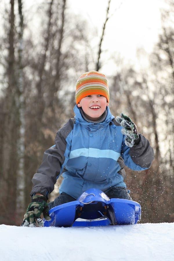 El muchacho piensa el mecanismo impulsor de la colina en invierno en los trineos imagenes de archivo