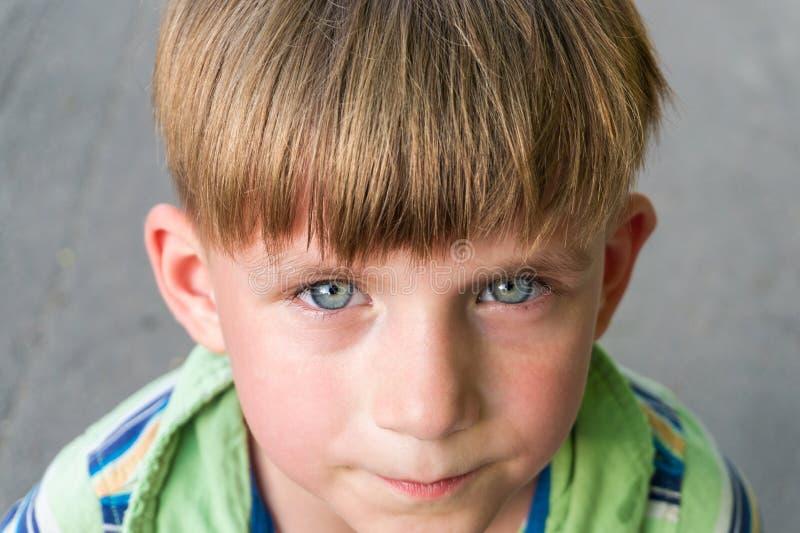 El muchacho pobre e infeliz llora con los rasgones en sus ojos y pide ayuda mientras que mira en la cámara fotos de archivo