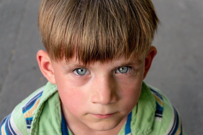El muchacho pobre e infeliz llora con los rasgones en sus ojos y pide ayuda mientras que mira en la c?mara imagen de archivo libre de regalías
