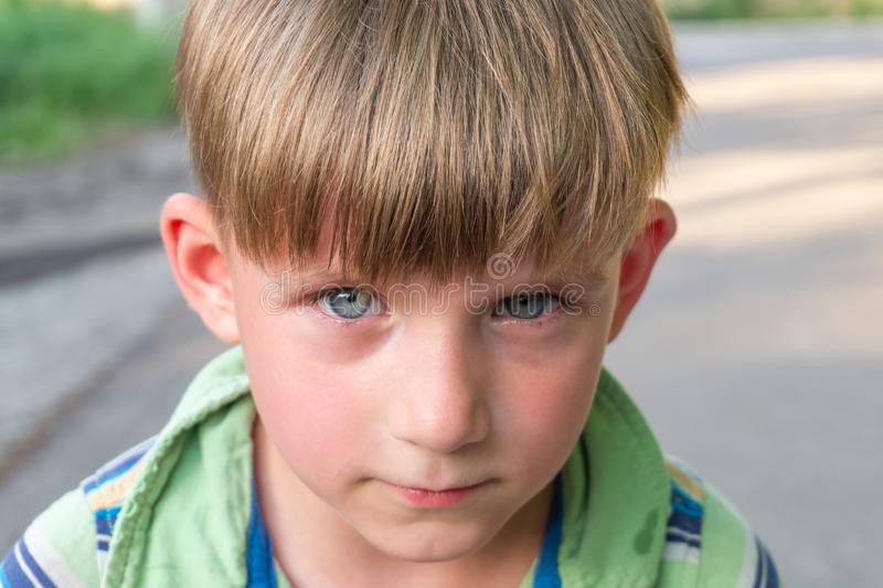 El muchacho pobre e infeliz llora con los rasgones en sus ojos y pide ayuda mientras que mira en la c?mara imagenes de archivo