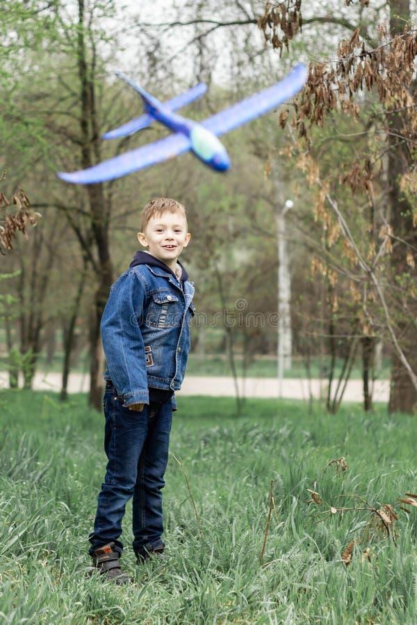 El muchacho pone en marcha un avi?n azul en el cielo en un bosque denso foto de archivo