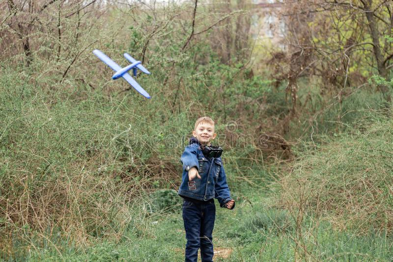 El muchacho pone en marcha un avi?n azul en el cielo en un bosque denso imagen de archivo libre de regalías