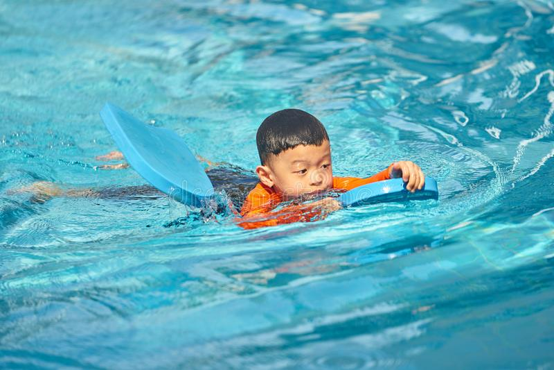 El muchacho practica el nadar con el flotador del cojín de goma espuma en agua fotos de archivo