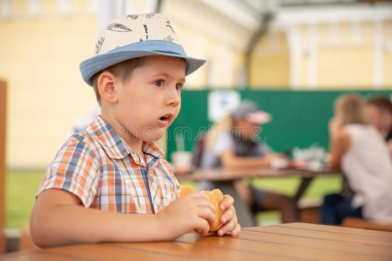 El muchacho preescolar del niño come la hamburguesa que se sienta en el café del cuarto de niños, muchacho feliz lindo que come l fotografía de archivo libre de regalías